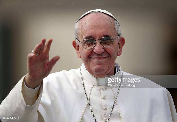 Pope Francis waves to the crowd as he drives around St Peter's Square ahead of his first weekly general audience as pope on March 27 2013 in Vatican...