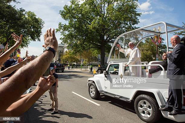 Pope Francis waves to the crowd as he rides in a popemobile along a parade route around the National Mall on September 23 2015 in Washington DC...