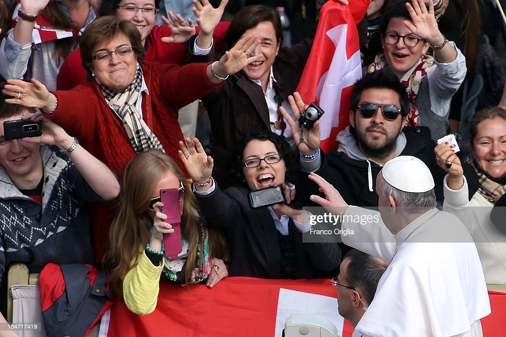 Pope Francis waves to the crowd from an open-air jeep, ahead of his first weekly general audience, in St Peter's Square on March 27, 2013 in Vatican City, Vatican.