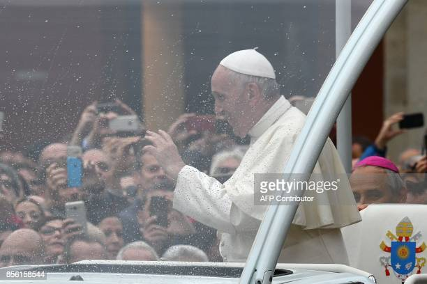 Pope Francis waves to the crowd from the popemobile as he arrives in Piazza Maggiore during a pastoral visit in Bologna on October 1 2017 / AFP PHOTO...