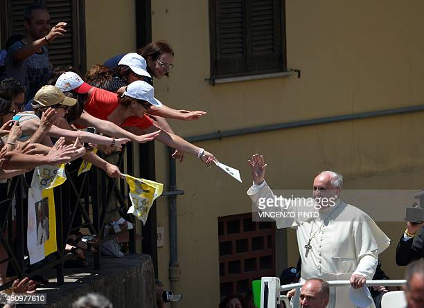Pope Francis waves to the crowd from the popemobile on June 21 2014 as he arrives in Cassano allo Ionio in the southern Italian region of Calabria...