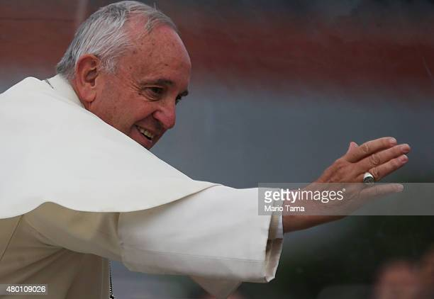 Pope Francis waves to the crowd from the Popemobile while making his way to celebrate an openair Mass on July 9 2015 in Santa Cruz Bolivia Pope...