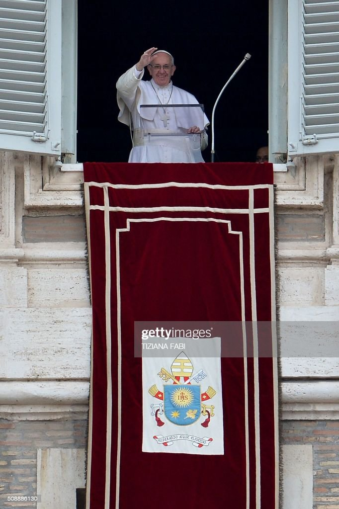 Pope Francis waves to the crowd from the window of the apostolic palace overlooking St Peter's square during the Sunday Angelus prayer, on February 7, 2016 in Vatican. / AFP / TIZIANA FABI