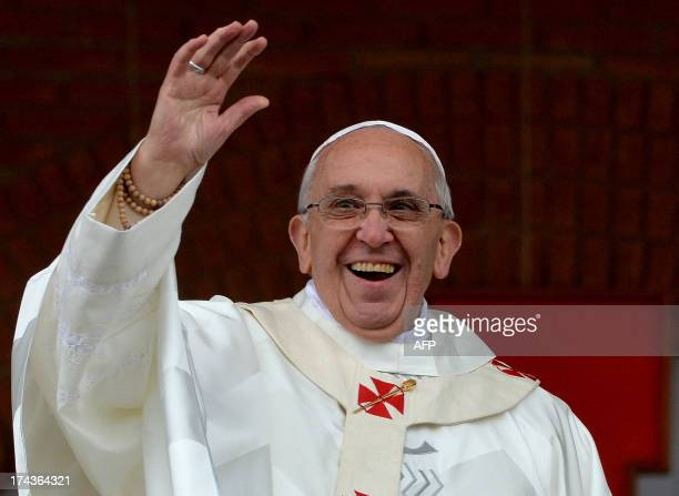 Pope Francis waves to the crowd gathering outside the Basilica of Our Lady of Aparecida Brazil's most revered Catholic shrine after he celebrated...
