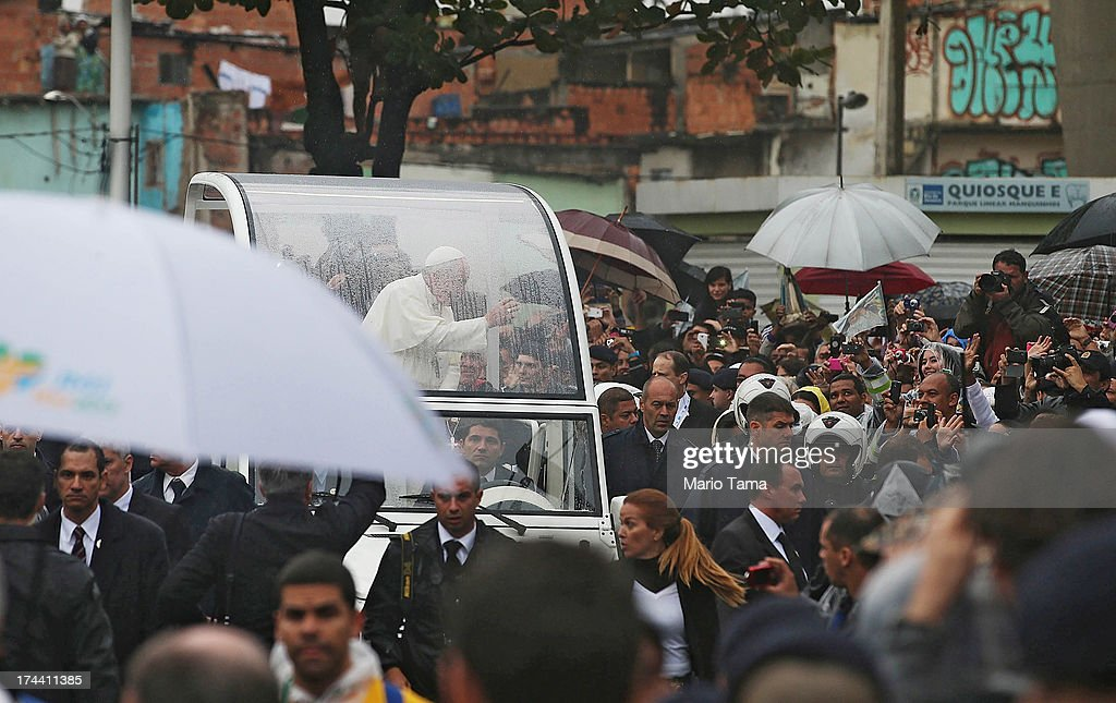 Pope Francis (L) waves to the crowd while riding in the Popemobile as he tours the Varghina favela, or shantytown, on July 25, 2013 in Rio de Janeiro, Brazil. More than 1.5 million pilgrims are expected to join Pope Francis for his visit to the Catholic Church's World Youth Day celebrations. Pope Francis will deliver his welcome address to the celebrations on Copacabana Beach later today as World Youth Day runs July 23-28.