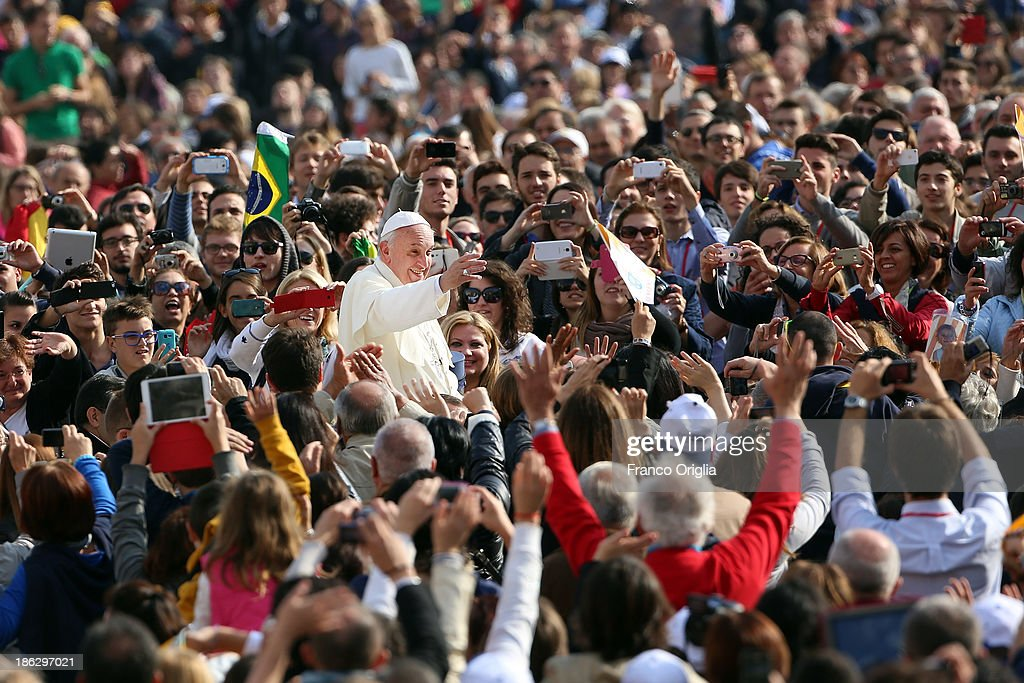 <a gi-track='captionPersonalityLinkClicked' href=/galleries/search?phrase=Pope+Francis&family=editorial&specificpeople=2499404 ng-click='$event.stopPropagation()'>Pope Francis</a> waves to the faithful as he arrives in the popemobile at St. Peter's Square for his weekly audience on October 30, 2013 in Rome, Italy. During the audience the pontiff continued his series of catechetical reflections on the Creed, focusing this week on the Communion of Saints.