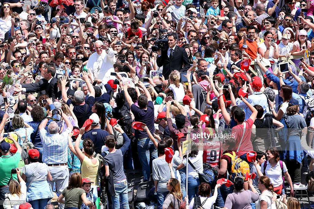 Pope Francis waves to the faithful as he attends the rite of Confirmation during a Mass at St. Peter's Square on April 28, 2013 in Vatican City, Vatican. The special Mass was organized as part of the Year of Faith, during which 44 people from all over the world received the Sacrament of Confirmation directly from the Pontiff.