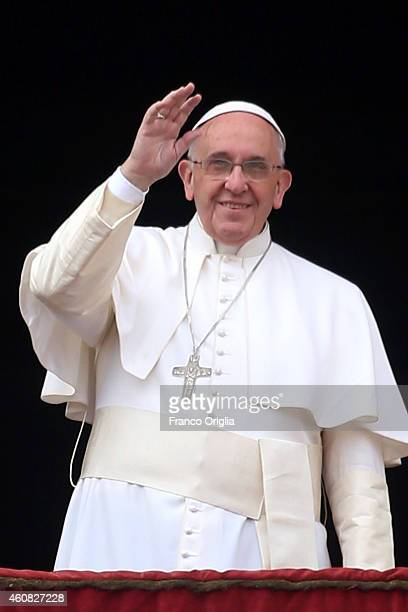 Pope Francis waves to the faithful as he delivers his Christmas Day message from the central balcony of St Peter's Basilica on December 25 2014 in...