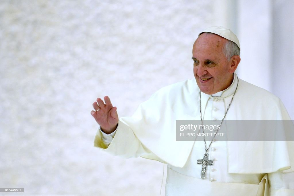 Pope Francis waves to the faithfulls gathered in the Paul VI hall prior to his meeting with the Italian Union for the transportation of sick people to Lourdes and International Shrines (UNITALSI) on November 9, 2013 at the Vatican.