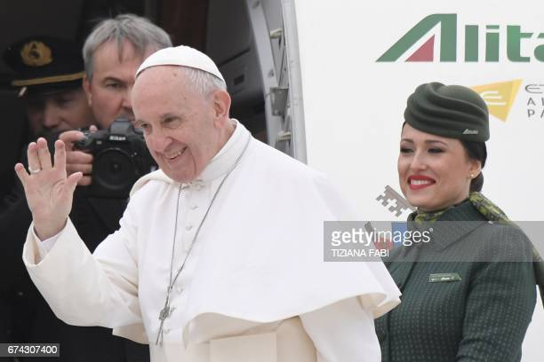Pope Francis waves to the press as he is welcomed by Alitalia's personnel prior his flight to Egypt on April 28 2017 at Rome's Fiumicino airport Pope...
