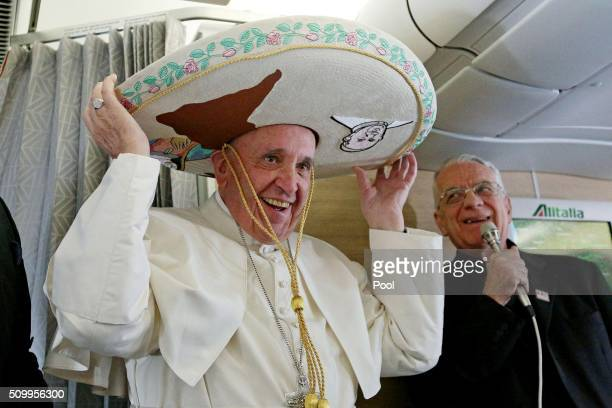 TOPSHOT Pope Francis wears a traditional Mexican sombrero hat received as a gift by a Mexican journalist on February 12 aboard the plane to Havana...