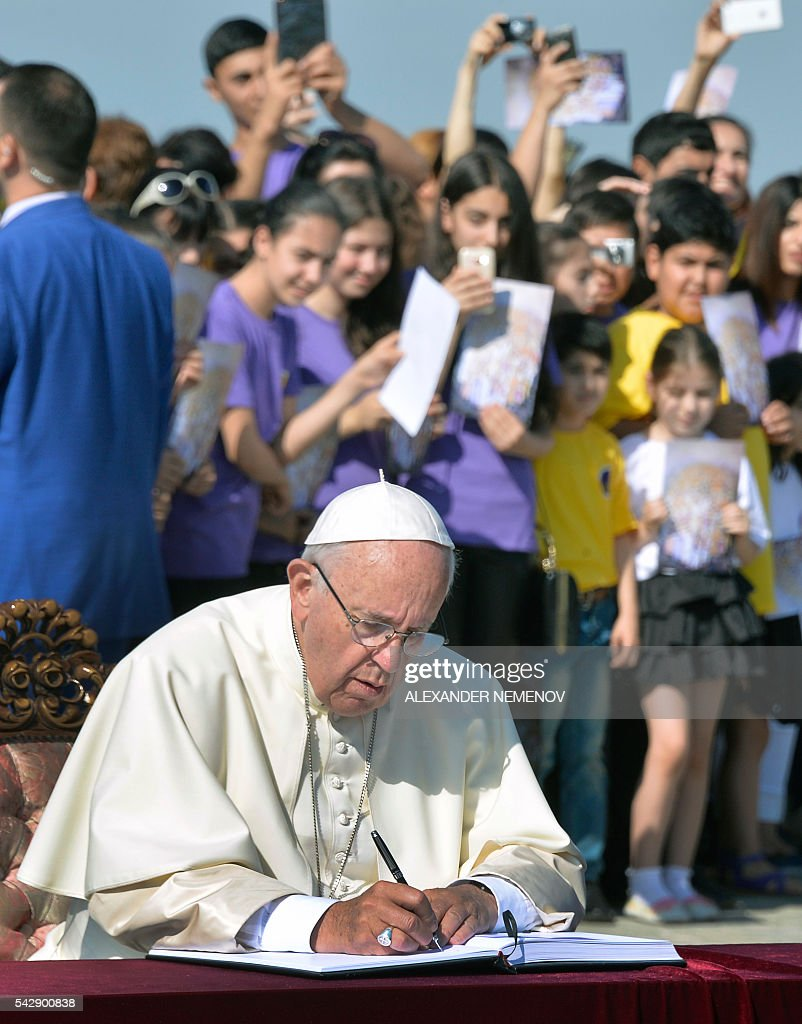 Pope Francis writes in a visitors' book as he visits the Tsitsernakaberd Armenian Genocide Memorial in Yerevan on June 25, 2016. / AFP / ALEXANDER