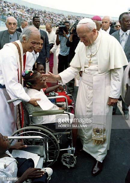 Pope John Paul II blesses a girl in a wheelchair 10 August 1993 before mass at National Stadium in Jamaica The Pope is scheduled to wind up his three...