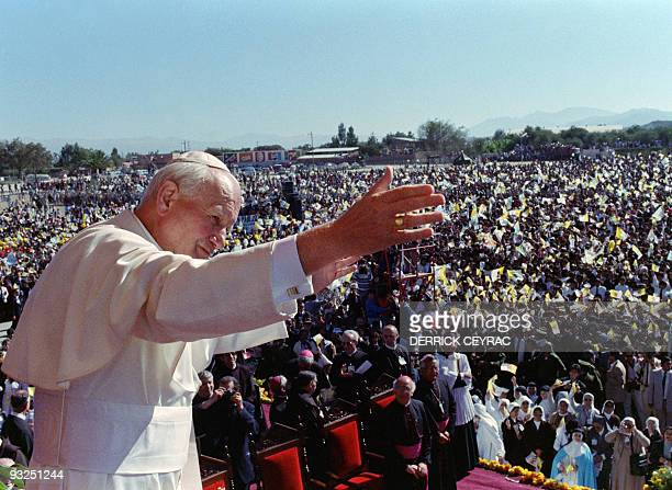 Pope John Paul II blesses Bolivian faithful 13 May 1988 at Tajira airport shortly before leaving the country for Paraguay during his 37th...