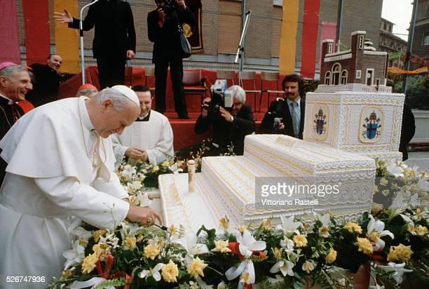 Pope John Paul II cuts a cake on his 60th birthday