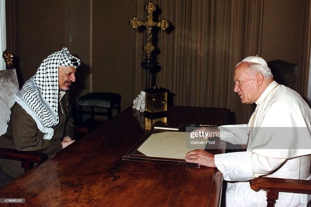 Pope John Paul II exchanges gifts with Palestinian leader Yasser Arafat at his summer residence on September 2, 1995 in Castel Gandolfo, Italy.