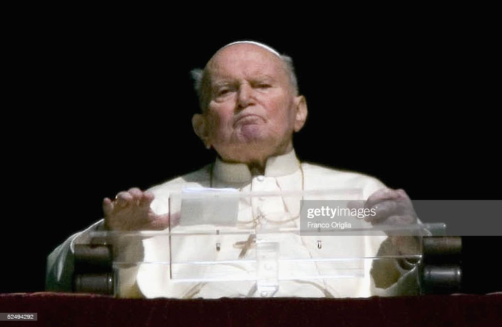 Pope John Paul II gives his blessing from his window to pilgrims and faithful gathered in St. Peter's Square on March 30, 2005 in Vatican City. The Roman Catholic leader, who had throat surgery last month, did not speak but made the sign of the Cross with his hand. The appearance came amid reports that doctors are considering inserting a feeding tube into his stomach, to aid his swallowing of food.