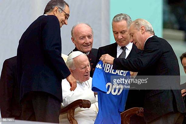 Pope John Paul II is presented with a souvenir at Rome's Olympic stadium October 29 to celebrate a mass for the athletes'' Jubilee The pope held a...