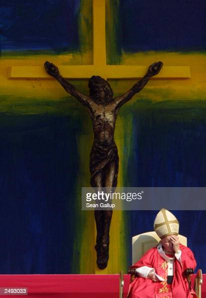Pope John Paul II rests his head in his hand under a giant crucifix during an outdoor mass September 14 2003 in Bratislava Slovakia The Pope...