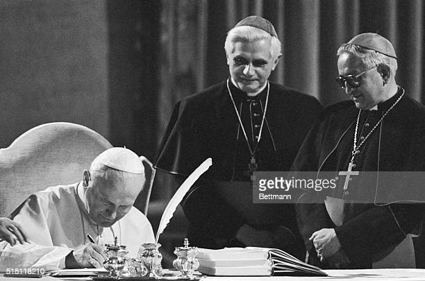 Pope John Paul II seated at a table in the Old Consistorial Hall signs the new Roman Catholic Code of Canon Law during a ceremony at the Vatican 1/25...