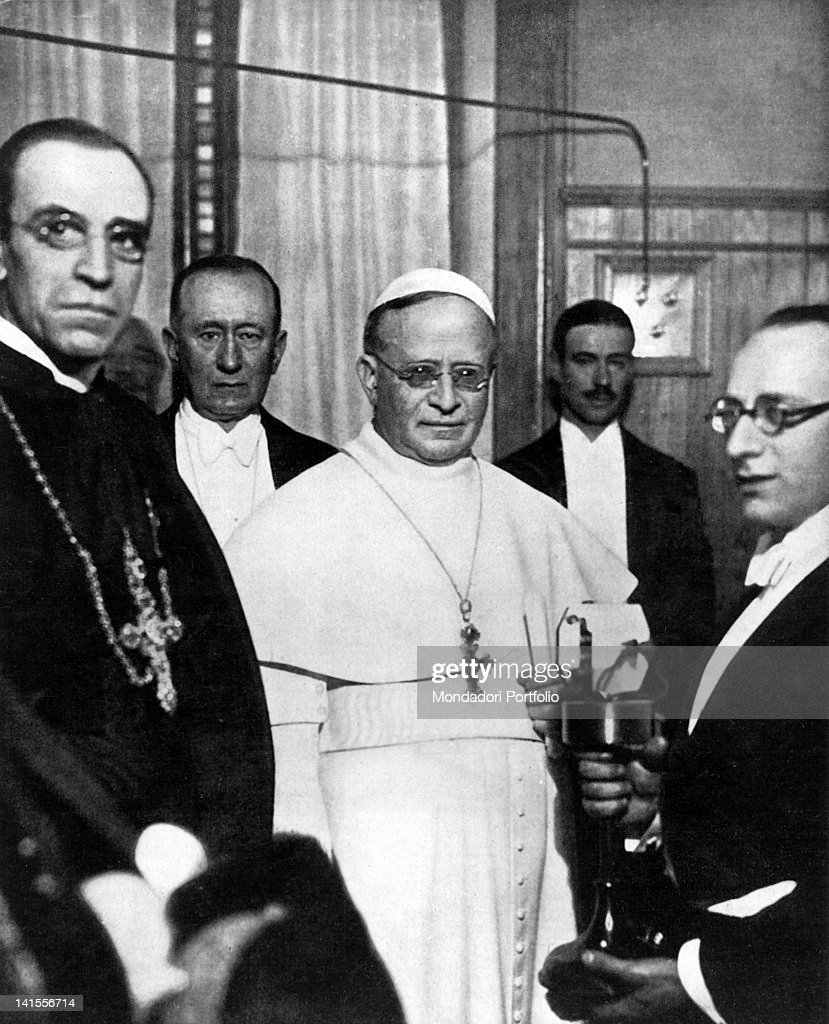 <a gi-track='captionPersonalityLinkClicked' href=/galleries/search?phrase=Pope+Pius+XI&family=editorial&specificpeople=93954 ng-click='$event.stopPropagation()'>Pope Pius XI</a> inaugurating Vatican Radio in the presence of Cardinal Eugenio Pacelli and <a gi-track='captionPersonalityLinkClicked' href=/galleries/search?phrase=Guglielmo+Marconi&family=editorial&specificpeople=91004 ng-click='$event.stopPropagation()'>Guglielmo Marconi</a>. Vatican City, 1931