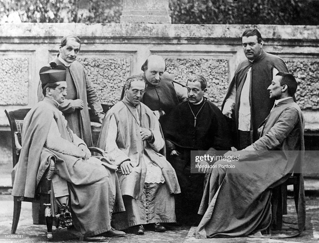 <a gi-track='captionPersonalityLinkClicked' href=/galleries/search?phrase=Pope+Pius+XI&family=editorial&specificpeople=93954 ng-click='$event.stopPropagation()'>Pope Pius XI</a> sitting together with clergymen. In the Twenties