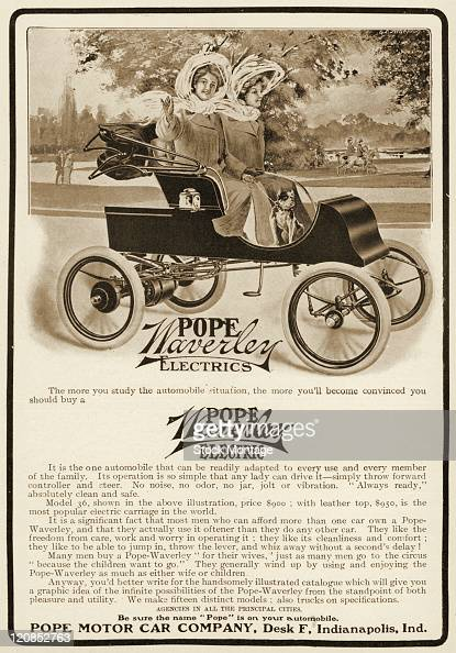 A PopeWaverly Electric automobile is shown in a magazine advertisement from 1905 Two young women are seated inside the car a small pet dog is near...
