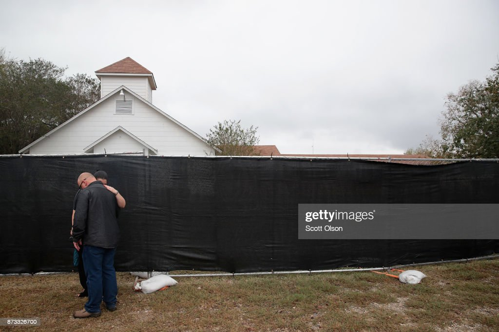 Pople embrace in front of the First Baptist Church of Sutherland Springs on November 12, 2017 in Sutherland Springs, Texas. The congregation held service today in a tent on the towns ball park. Today the original church will open to visitors as a memorial to the victims who were shot during last Sunday's service. Residents of the community are still trying to heal following the shooting. Devin Patrick Kelley shot and killed the 26 people and wounded 20 others when he opened fire during Sunday service at the church.