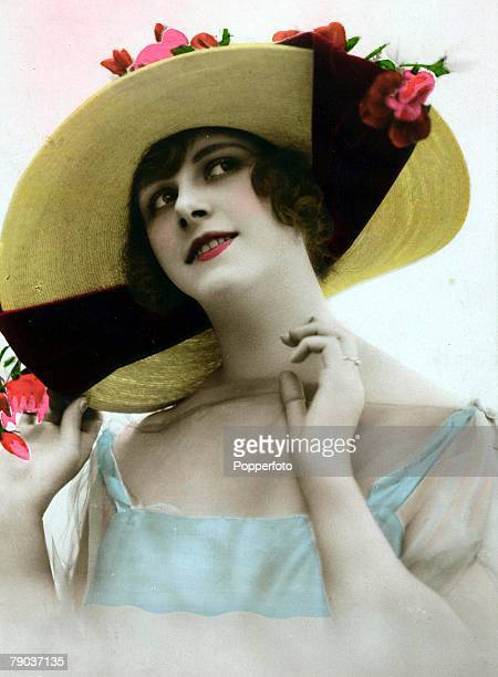 Popperfoto The Book Volume 1 Page 53 Picture 7 A picture of a woman wearing a light fashionable dress whilst displaying her new large rimmed hat...