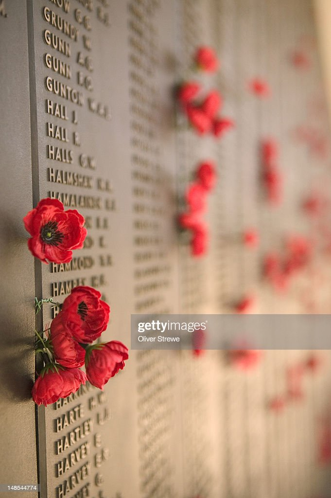 Poppies and lists of names on the memorial wall for Australian soldiers who died in the Second World War - Australian War Memorial.