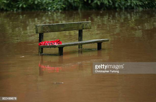 Poppies are left on a bench as floodwaters rise after rivers burst their banks on December 26 2015 in Hebden Bridge England There are more than 200...