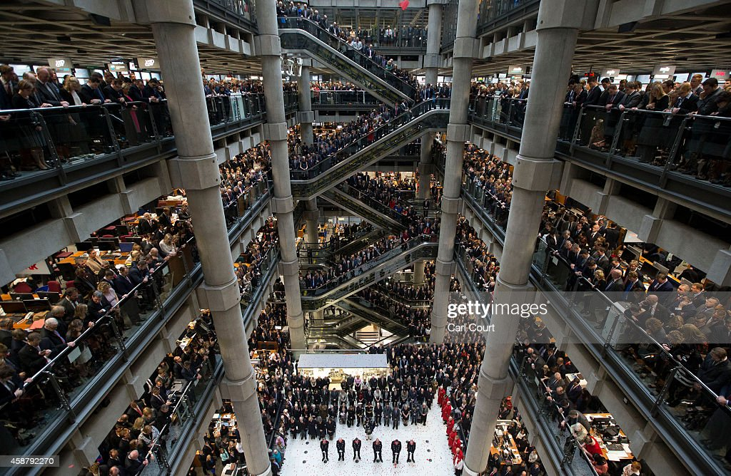 Poppies fall during a twominute silence at a Remembrance Day service at the Lloyd's of London building on November 11 2014 in London United Kingdom...