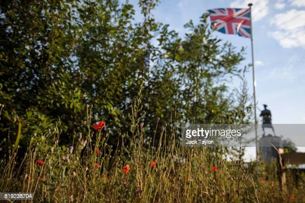 Poppies grow beside a field near Polygon Wood as a Union Flag flutters in the wind by a war memorial on July 13 2017 in Ypres Belgium July 31 2017...