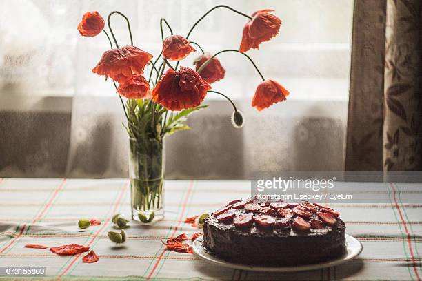 Poppies In Vase By Cake On Table At Home