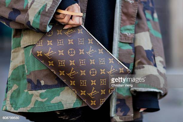 Poppy Bai wearing a Kayne West camouflage jacket Louis Vuitton clutch and capt outside during London Fashion Week Spring/Summer collections 2017 on...