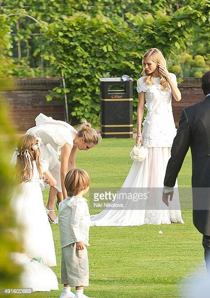 Poppy Delevingne and Cara Delevingne are seen at Poppy Delevingnes and James Cook's wedding reception held in Kensington Palace Gardens on May 16...