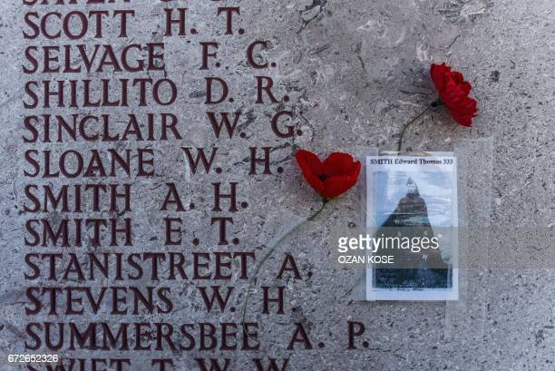 TOPSHOT Poppy flowers are placed between tiles of a wall containing the names of soldiers missing in action from World War One before the...