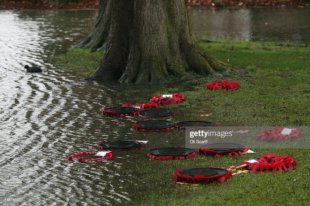 Poppy wreaths are washed away from a war memorial by flood waters from the River Thames on December 29, 2012 in Caversham, England. The Environment Agency has issued widespread flood warnings across the UK whilst the Met Office has predicted further rain forecast for the remainder of 2012, which is likely to be recorded as the wettest year since records began in 1910.