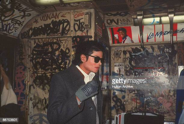 Popular American musician Michael Jackson stands in a graffitifilled subway car during the filming of the longform music video for his song 'Bad'...