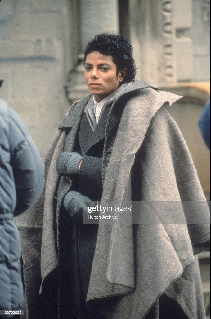 Popular American musician Michael Jackson stands with a blanket over his shoulders during a break in the filming of the longform music video for his...