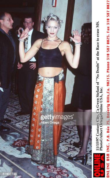 Popular American singer Gwen Stefani of the band No Doubt dressed in an orange and silver patterened sarong and a black midriffbaring tank top...
