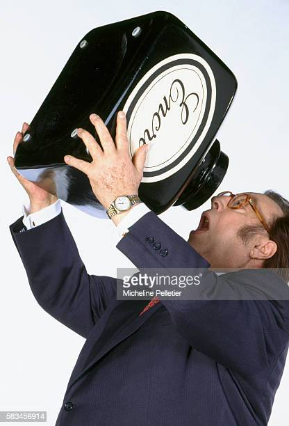 Popular Belgian comedian Raymond Devos pretends to drink ink from an oversized ink bottle Devos is author of the 1996 book Un Jour Sans Moi