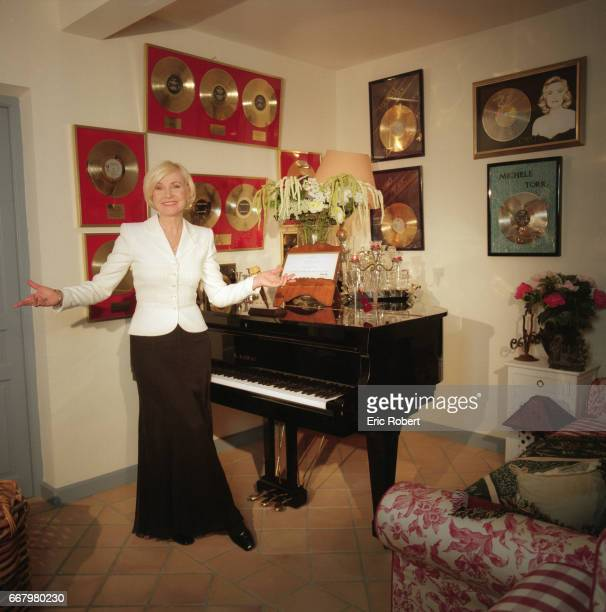 Popular French singer Michele Torr next to a baby grand piano in her music room She has numerous gold records displayed on the walls