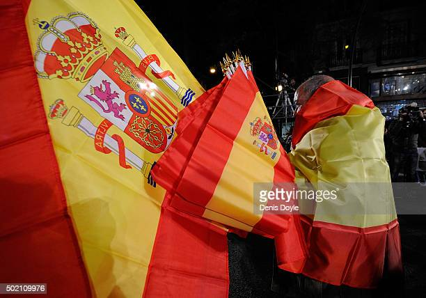 Popular Party supporter is wrapped in Spanish flags while waiting the results to come in outside party headquarters after General Elections were held...