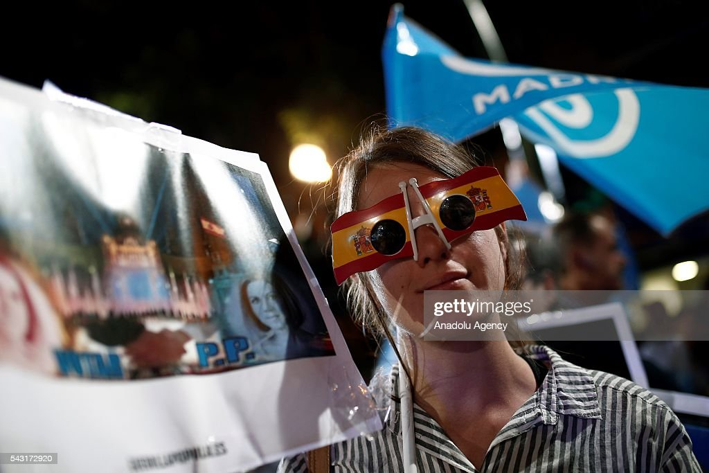 Popular Party supporters wave flags outside their headquarters after polls closed in the Spanish general election on June 26, 2016 in Madrid, Spain.