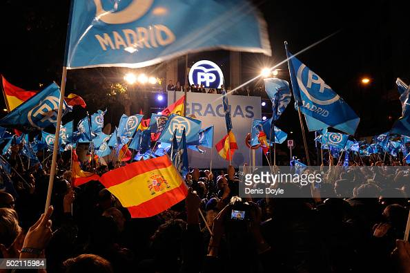 Popular Party supporters wave to Spanish Prime Minister Mariano Rajoy on the balcony at Popular Party headquarters after his party won the most votes...