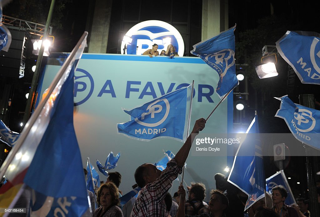 Popular Party supportes wave flags outside their headquarters after polls closed in the Spanish general election on June 26, 2016 in Madrid, Spain. Spanish voters headed back to the polls on June 26 after the last election in December failed to produce a government. Latest opinion polls suggest the Unidos Podemos left-wing alliance could make enough gains to come in second behind the caretaker government of the center-right Popular Party.