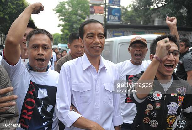 Popular presidential candidate of main opposition party Indonesian Democratic Party of Struggle and Jakarta Governor Joko Widodo walks with his...