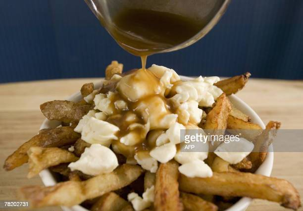 A popular Quebec dish called Poutine consisting of french fries cheddar cheese and gravy 20 November 2007 in Montreal Quebec Canada The traditional...