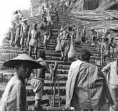 Population de porteurs grimpant les escaliers qui permettent l'accès à la ville à Chongqing Chine circa 1910